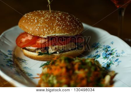 Burger with chicken tomatoes parsley and bun with sesame seeds on a oval plate with a blue ornament. Next - a carrot and cucumber salad and glass of beer on the leg.