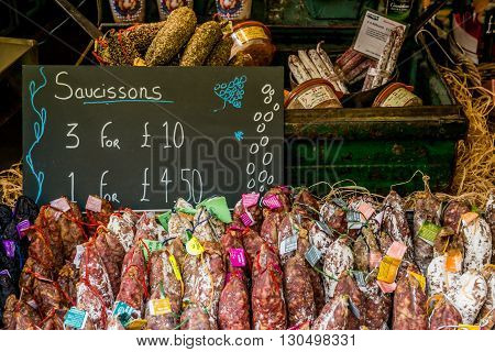 London United Kingdom - May 14 2016: Brixton Village and Brixton Station Road Market. Colorful and multicultural community market run by local traders in South London. French saucissons - sausages