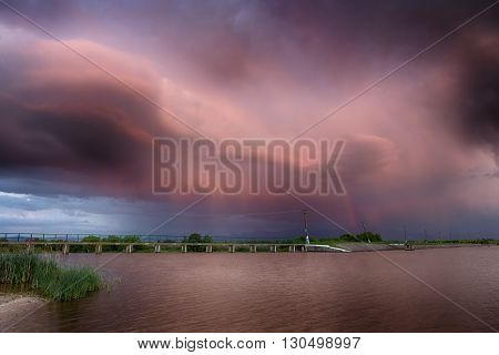Red Sky. On The Lake. Rainbow. Red Sunset After The Rain. Low Key, Dark Background, Spot Lighting, A