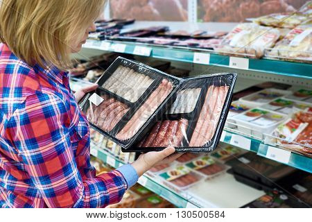 Woman Chooses Sausages For Barbecue In Store