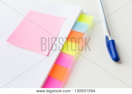 business, information, memo, management and education concept - close up of notebook or organizer with blank tags and sticker and pen on office table