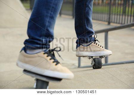 closeup of skateboarder legs skateboarding at skatepark ramp