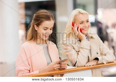sale, consumerism, technology and people concept - happy young women with smartphones and shopping bags in mall