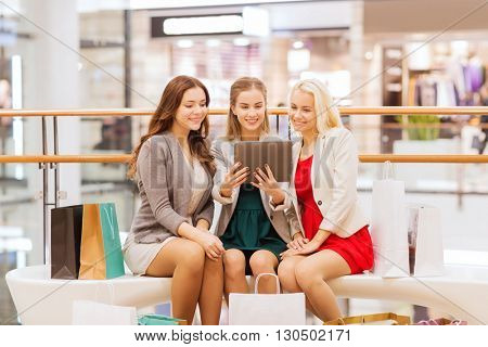 sale, consumerism, technology and people concept - happy young women with tablet pc and shopping bags in mall