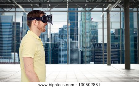 3d technology, virtual reality, entertainment and people concept - happy young man with virtual reality headset or 3d glasses playing game over industrial empty room and city panorama background