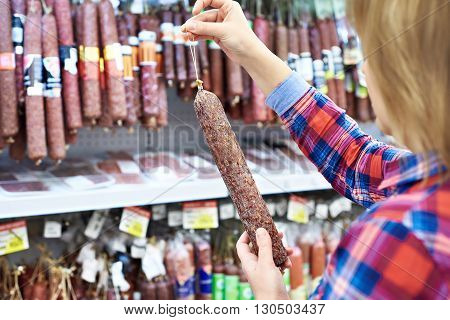 Woman Chooses Smoked Sausage In Store