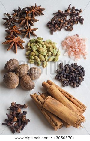 A selection of spices - cloves cinnamon bark black pepper corns whole nutmegs cardamom pods star anise - with pink rock salt crystals.