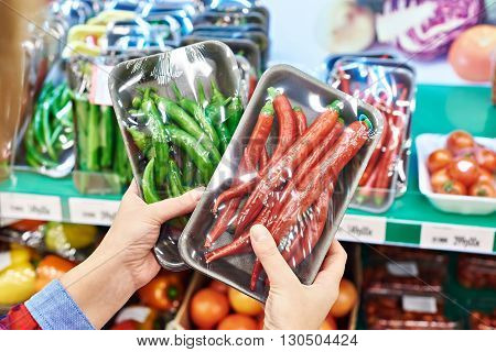 Buyer Selects Chili Peppers In Store