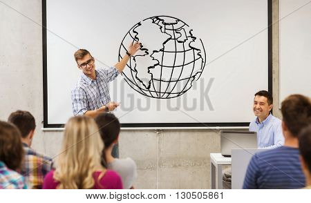education, high school, geography and people concept - student standing with remote control in front of teacher and classmates in classroom and showing earth globe drawing on white board in classroom