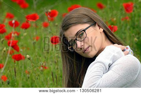 Portrait of young girl in poppy flowers field