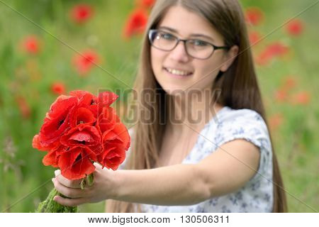 Young girl with poppy bouquet on field