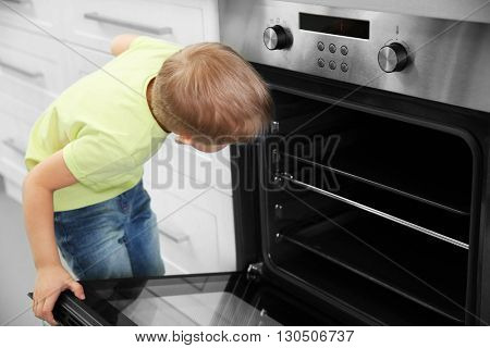 Little child playing with electric stove in the kitchen