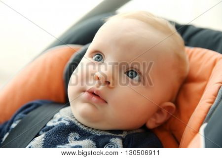 Adorable baby boy sitting in car seat