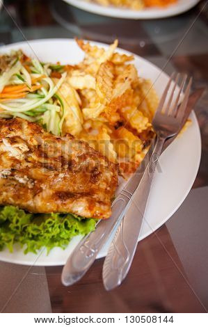 Fresh bbq barracuda fish fillet.Traditional khmer cambodian cuisine served with chips and salad.