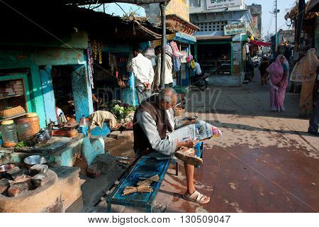 CHITRAKOOT, INDIA - DEC 29, 2012: Old asian man reading a morning newspaper on December 29, 2012 in Chitrakoot India. Chitrakoot has an average literacy rate of 50 perc lower than the national average of 59.5 perc.