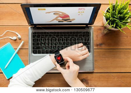 healthcare, fitness, people and technology concept - close up of woman with smart watch and laptop computer on wooden table with sport application and heart rate on screens
