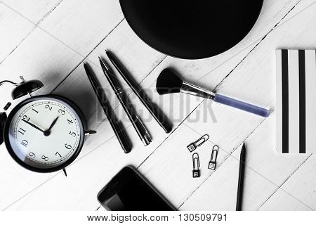 Black colour flat lay composition on white wooden background, top view