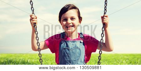 summer, childhood, leisure, friendship and people concept - happy little girl swinging on swing over blue sky and grass background