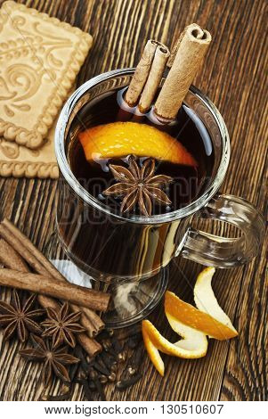 Hot spiced mulled wine garnish with orange and biscuits on a wooden background
