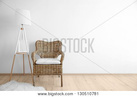 Cozy chair with lamp on wall background