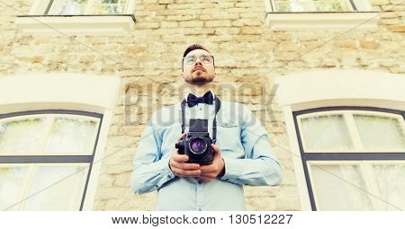 people, photography, technology, leisure and lifestyle - happy young hipster man with retro vintage film camera on city street