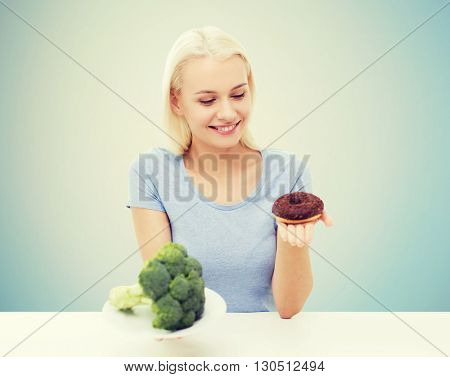 healthy eating, junk food, diet and choice people concept - smiling woman choosing between broccoli and donut over blue background