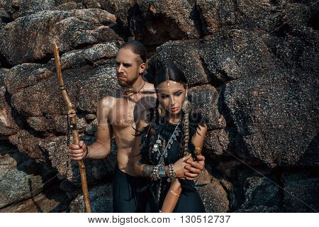 Attractive tribal man and woman in ethnic jewelry outdoors