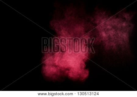 Red and pink powder explosion on black background. Colored powder cloud. Colorful dust explode. Paint Holi.