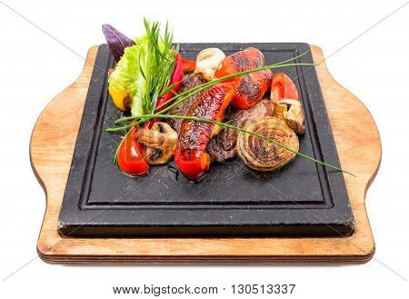 Mexican beef steak with grilled onions and red paprika on grill metal pan. Decorated with fresh herbs. Isolated on a white background.