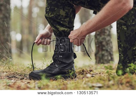 war, hiking, army and people concept - close up of soldier boots and hands tying bootlaces in forest