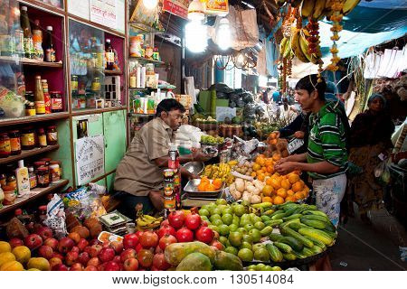 KOLKATA, INDIA - JANUARY 16, 2013: Customer buys fruit in the colorful city market on January 16, 2013 in Kolkata, India. Only 0.81 perc. of the Kolkata's workforce employed in the primary sector - agriculture