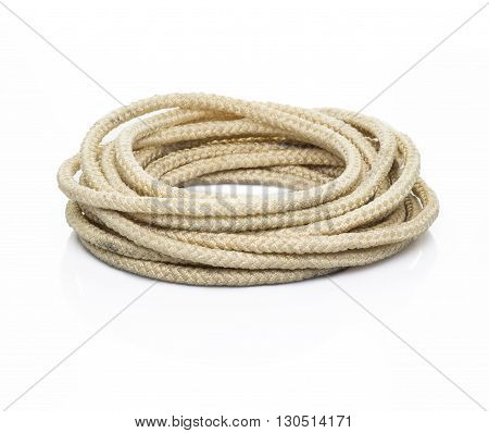 Hemp three strand rope coiled in a circluar pattern isolated against a white background