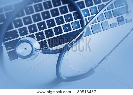 Laptop Computer and Stethoscope in Doctor Office. Computerized Health Care Medical Center