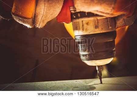 Electric Drill and Screw. Small Construction Works Closeup Photo.
