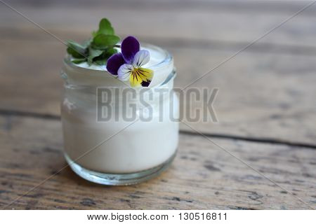 Face cream in a glass jar with a violet flower on a wooden board. Cosmetics.