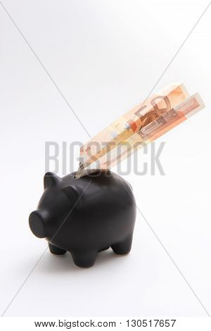 A black piggybank with money on a white background