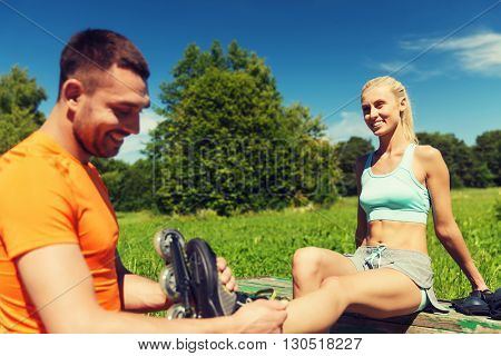 fitness, sport, summer, couple and healthy lifestyle concept - happy man helping woman to put on rollerskates outdoors