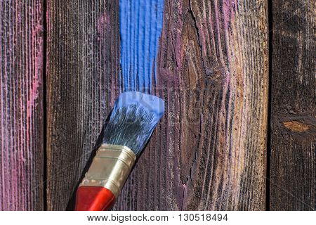 Brush and a smear of blue paint on old wooden texture