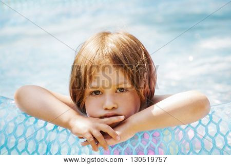 Thoughtful little girl in the pool outdoor.