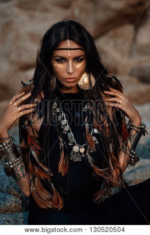 Attractive tribal woman in ethnic jewelry posing outdoors