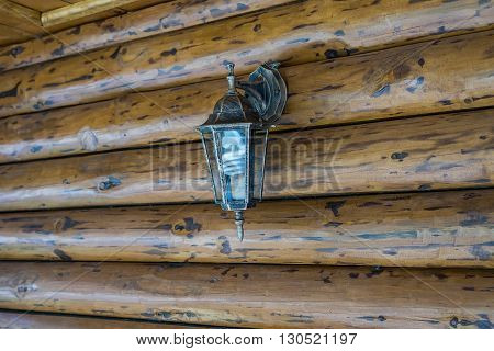 Lamp on the porch of the cottage made of logs of wood with energy-saving light bulb