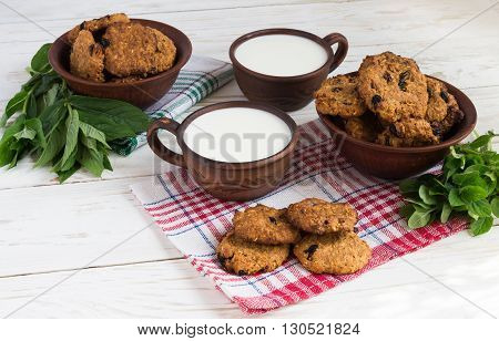 Old ceramic cups of milk and freshly baked oatmeal raisin cookies