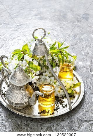 Tea glasses and pot. Oriental holidays decoration. Silver tea dishes. Herbal tea