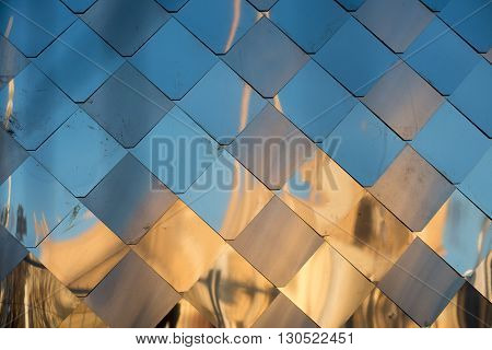 old, dirty aluminum metal wall facade panel with rhombus, similar to the scales and tiles. Reflection of sunset