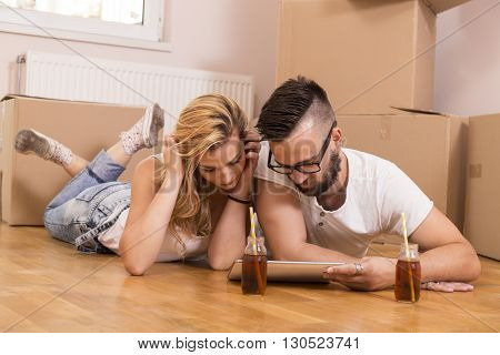 Young couple in love moving in a new flat lying on the floor and surfing the web on a tablet computer in search of new redecoration ideas