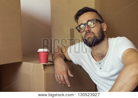 Young man moving in a new appartment sitting on the floor drinking take away coffee surrounded with cardboard boxes