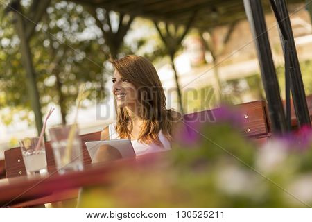 Beautiful brunette sitting in an outdoor cafe reading an e-book on her tablet computer and drinking lemonade