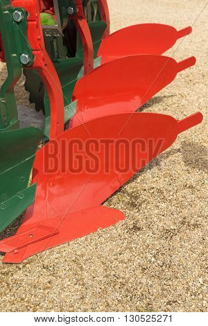 Detail of red plough for a Farming Tractor