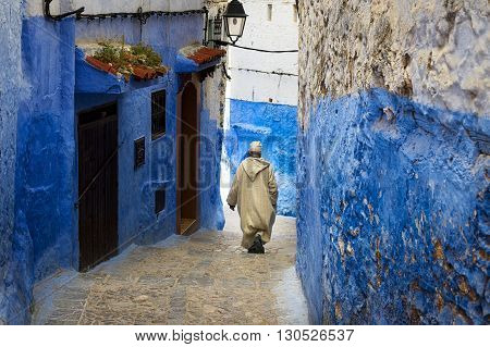 Chefchaouen Morocco - April 10 2016: A man walking in a street of the town of Chefchaouen in Morocco.