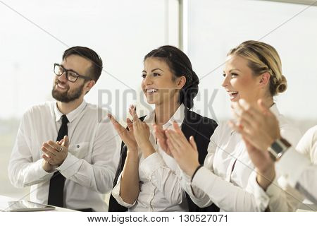 Business team applauding a colleague on a successful presentation